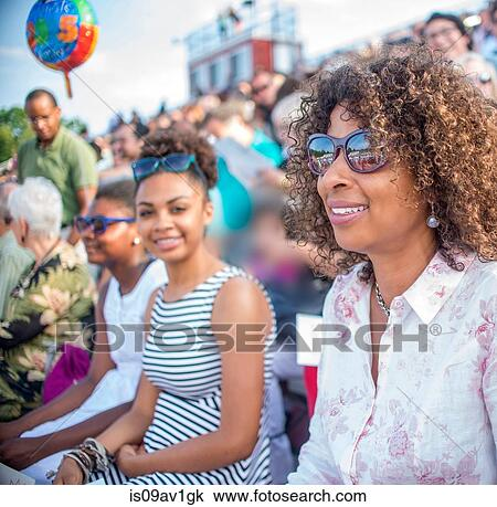95b7b70fb5f Stock Photo of Mature mother and daughters watching graduation ...