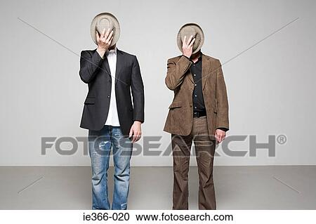 stock photography of men holding hats over their faces ie366 020