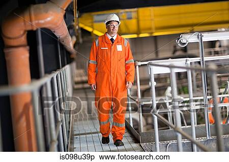 stock image of engineer walking along walkway in factory is098u39p