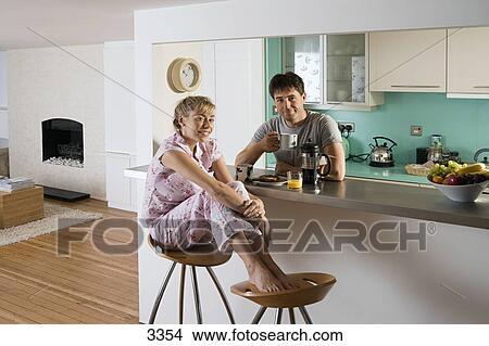 Archivio fotografico coppia in pyjamas seduta a cucina