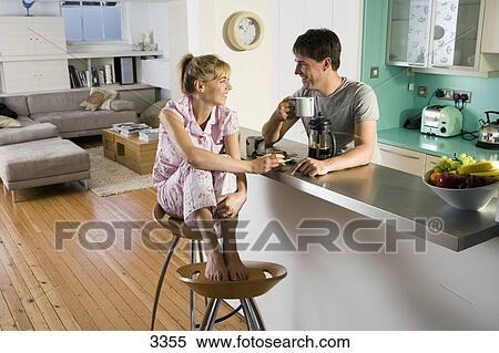 Archivio immagini coppia in pyjamas seduta a cucina sbarra
