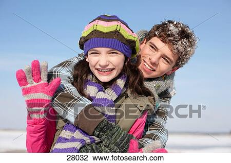 stock photo of happy teenage boy and girl hugging on winter day