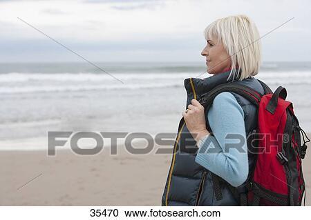 af23de8f6 Colección de imágen - mujer madura, andar playa, con, mochila. Fotosearch