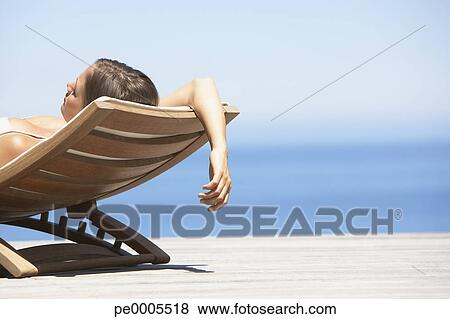 Brilliant Woman Sunbathing On Folding Chair Outdoors Stock Photo Gmtry Best Dining Table And Chair Ideas Images Gmtryco
