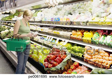stock image woman in grocery store with shopping list smiling fotosearch search stock