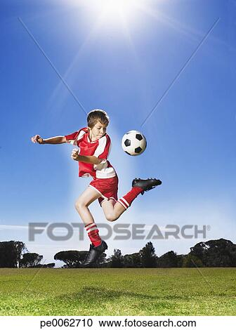 stock photography of young boy in uniform kicking soccer ball