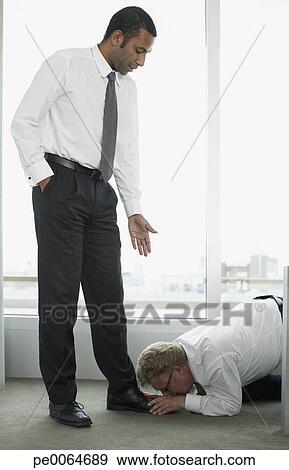 stock photograph of businessman kissing boss feet pe0064689