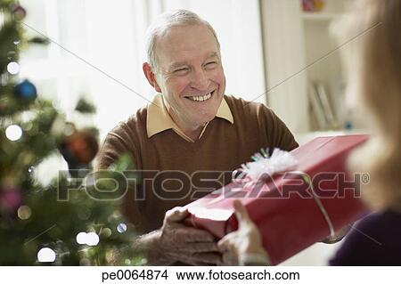senior man giving wife christmas gift