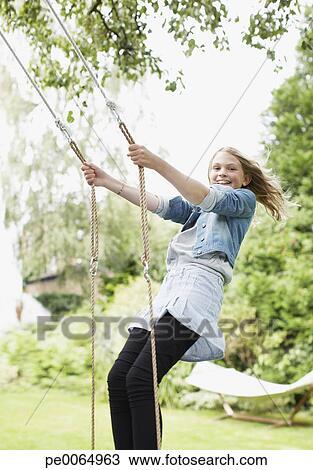 Girl standing on swing in backyard Stock Image | pe0064963 ...