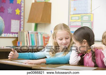 Girl cheating from friend's paper on test Stock Image
