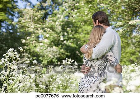 Stock Images Of Couple Hugging In Field Of Flowers Pe0077676
