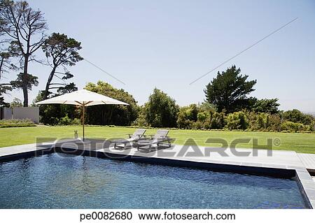 Swimming pool, lounge chairs and umbrella Stock Image