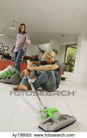 Stock Image Of Mother And Son In Living Room Vacuum Cleaner
