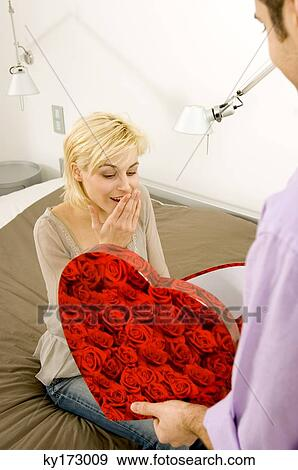 Stock Photograph Young Man Giving A Gift To Woman Fotosearch Search