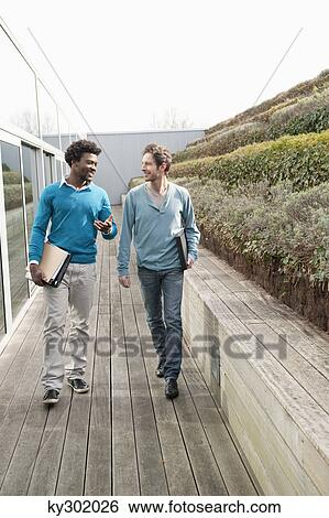 stock images of two friends walking together on a boardwalk ky302026