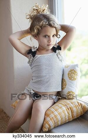 stock image of cute little girl sitting on the window ky334045