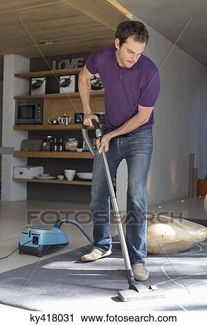 Stock Photography Of Man Cleaning Living Room With Vacuum Cleaner