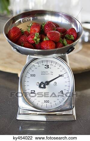 stock photo of strawberries on a weighing scale at a kitchen counter