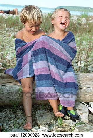 pictures of girl and boy in bath towel sitting on log smiling