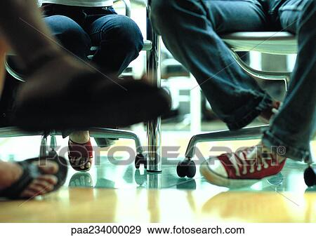 Stock Photograph of Legs and feet view under table paa234000029