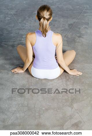 stock photo of woman sitting indian style on floor rear