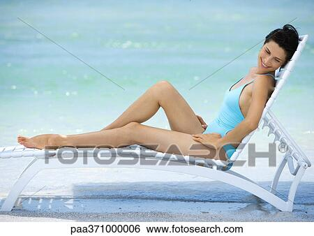 Woman Sitting In Lounge Chair On Beach