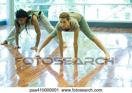 two young adults doing prasarita padottanasana pose in