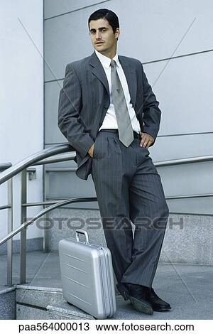 stock photo of businessman leaning against railing briefcase on