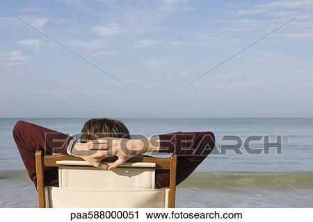 Person Relaxing In Chair On Beach Rear View