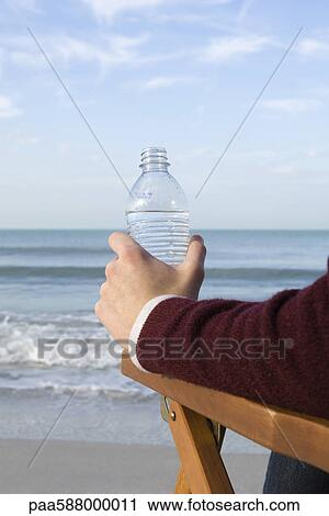 stock photography of person sitting relaxing at the beach water