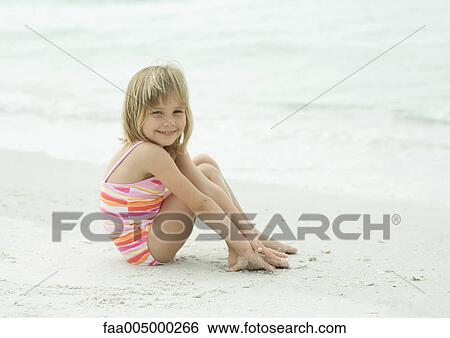 Little Girl Sitting On Beach With Knees Up Smiling At Camera Stock