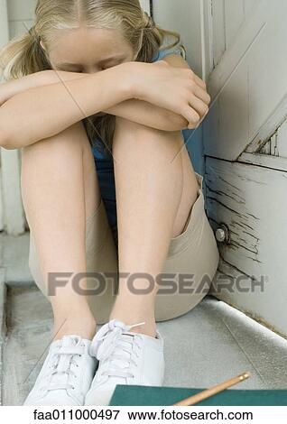 Girl Sitting With Knees Up And Head Down Stock Photo Faa011000497