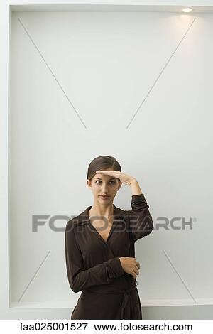Gesture, teenage girl, standing, looking out, shading eyes, body language,  curiosity Stock Photo