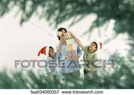 picture young man holding tall stack of christmas gifts boys placing more gifts on