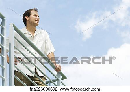 stock photo of man leaning against railing looking into distance