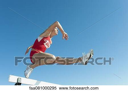 Famale Athlete Jumping Over Hurdle Low Angle View