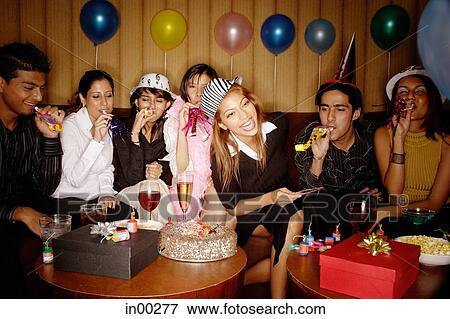 Picture Of Young Adults Celebrating Birthday Wearing Party Hats