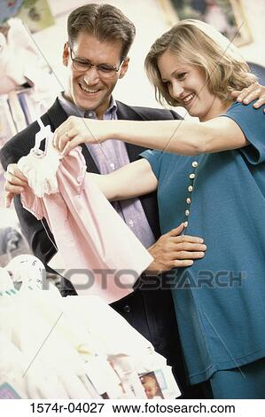 Pregnant Woman With Her Husband Shopping For Baby Clothes Stock Photo 1574r 04027 Fotosearch