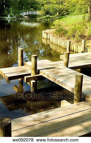 Japanese zen garden boardwalk over koi pond arched moon bridge in  background Stock Photo
