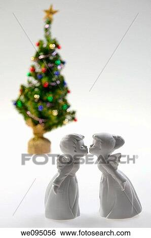 White porcelain boy and girl angels kissing in front of a decorated Christmas Tree