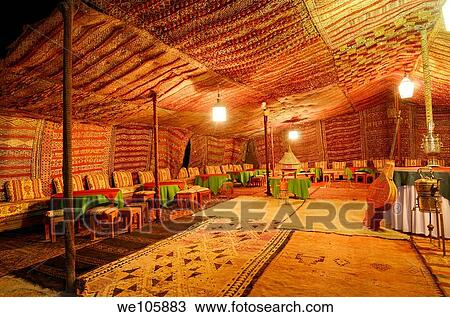 stock photo of large empty carpeted berber tent at night in tinerhir