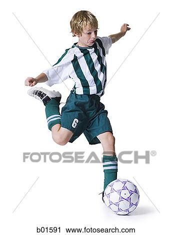 stock photography of boy kicking a soccer ball b01591 search stock