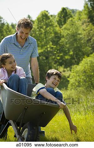 Man Pushing His Son And Daughter In A Wheelbarrow Stock Photography