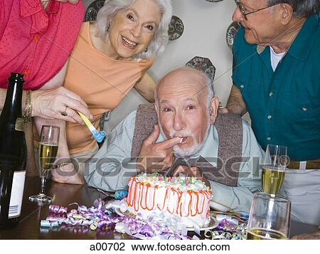 Partygoers Around A Birthday Cake