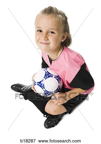 09e35fad0 Stock Photo - Young girl in a soccer uniform with ball.. Fotosearch