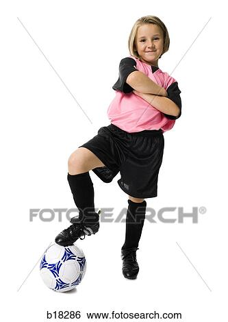 84b6a3a82 Stock Photograph - Young girl in a soccer uniform with ball.. Fotosearch