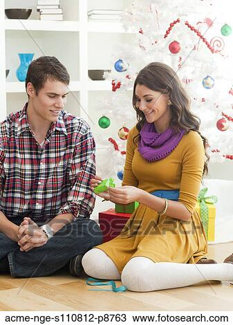 stock photo young couple sitting under christmas tree opening christmas present fotosearch
