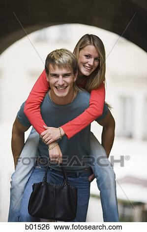 Portrait of a teenage boy giving a piggyback ride to a teenage girl Stock  Photograph