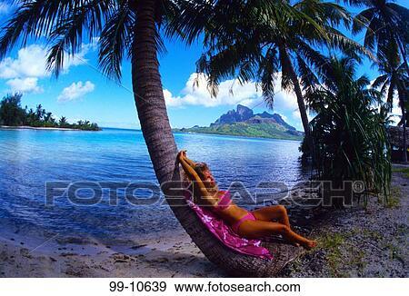 Woman Leaning Against A Palm Tree On The Beach Bora Bora