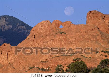 A full moon sits high above the Kissing Camels formation in the Garden of  the Gods city park, Colorado Springs, CO Stock Photo